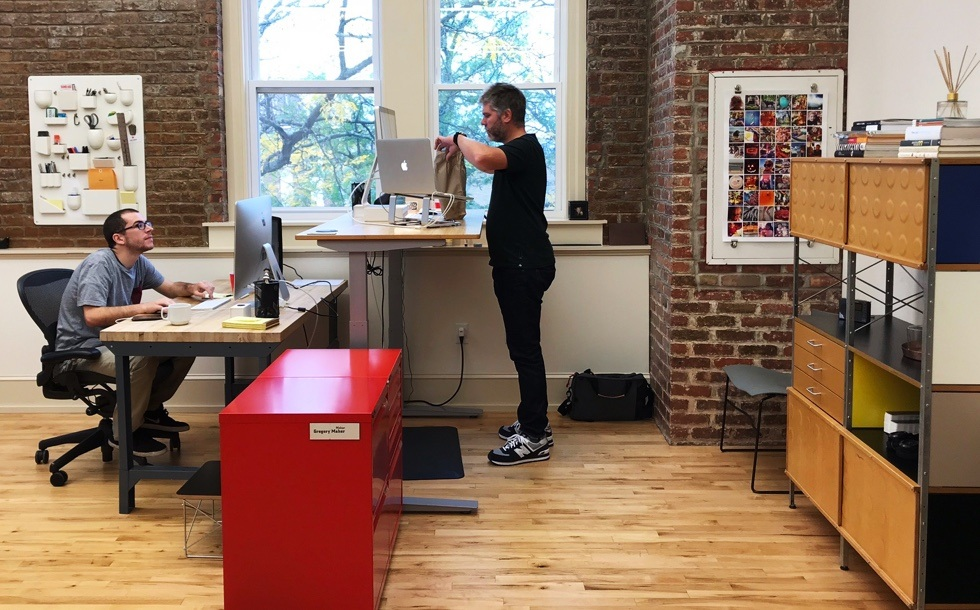 Alex sitting at his desk and Greg standing at his standing desk